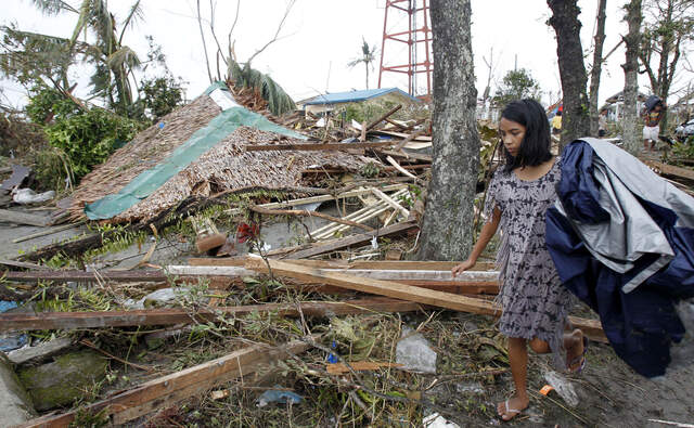 A resident walks past her collapsed house after super Typhoon Haiyan battered Tacloban city (Quelle: qSBSb21lbyBSYW5vY28gLyBSZXV0ZXJz)